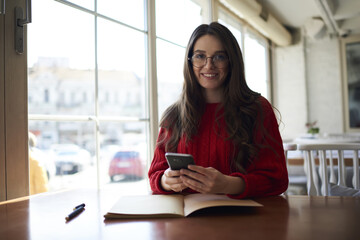 Portrait of smiling beautiful professional journalist looking at camera while checking latest news on websites and gathering information for next article on smartphone connected to 4G internet