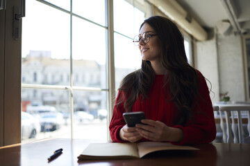 Charming young female author planning working strategy for next book and pondering about title page while sitting in cafe with loft interior,teen pretty hipster girl enjoying leisure time indoors