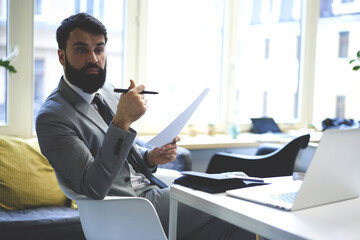 Beared elegantly dressed businessman checking documentation and report sitting in coworking office, experienced handsome lawyer checking contract for signing holding papers in coworking space