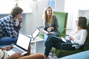 Group of young skilled students communicating with each other and sharing opinions about coursework for university while searching useful information in websites on laptop connected to 4G wireless