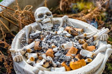 Skull ashtray with many cigarettes in this