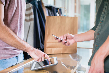 Customer paying with mobile phone in clothes shop