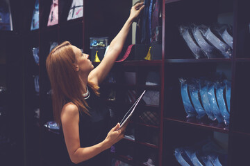 Portrait of a businesswoman checks availability of goods by using the touch pad while standing in her modern shop, young female consultant holding digital tablet during work in fashionable boutique