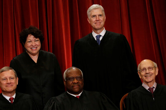 Gorsuch smiles as he joins his fellow justices for a new U.S. Supreme Court family photo including him, their most recent addition, at the Supreme Court building in Washington