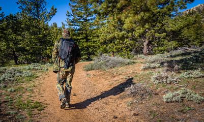 A man photographer hiking in camouflage outfit discovering nature in the forest with DSLR photo camera, lenses, tripod in the backpack. Travel photography lifestyle concept. Rear view