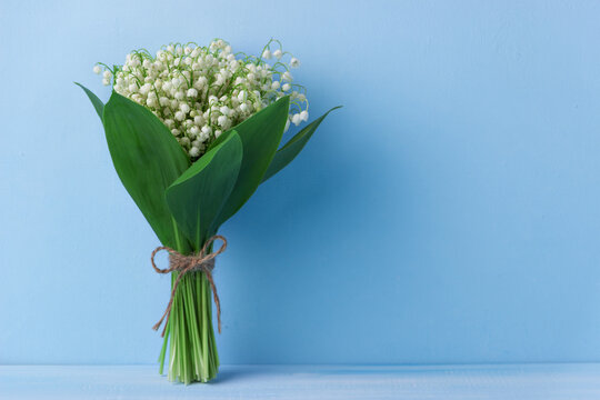 Lily of the valley on dark wooden background. Lily of the valley bouquet. Space for text.