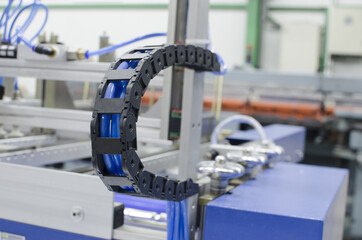 Industrial machine flexible power trak wire tray moving mechanism detail, selective focus copyspace background