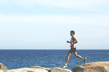 Full length portrait of handsome mature sports man running along the seashore while listening to music in headphones, male jogger while jumping over sea rocks while training hard outdoors in sunny day