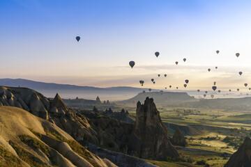Hot air ballooning in the golden light of sunrise, above the Cappadocian landscape.