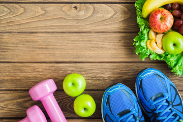 Fitness, healthy and active lifestyles Concept, dumbbells, sport shoes,  smartphone, fruits and vegetable on wood background. copy space, top view