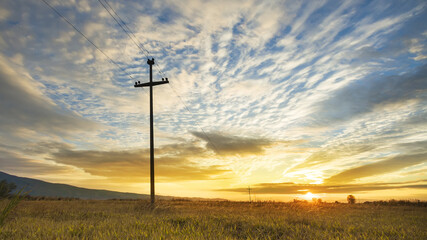 Electricity pole and harvest field on colorful sky, sunset