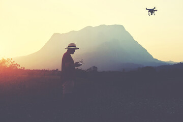 Young man traveler is shooting video on multirotor, while is standing in rural against high mountains in evening. Male wanderer is using radio-controlled quadcopter during his summer weekend abroad