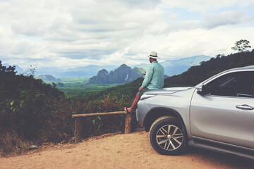 Young man wanderer is enjoying beautiful landscape during summer adventure on rental automobile in Asia. Male traveler is dreaming about something, while is sitting on a car hood against Amazon view