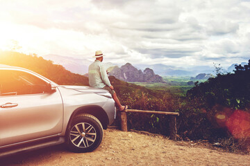 Dreaming man traveler is enjoying freedom and fantastic jungle view, while is sitting on a car hood in summer evening. Young male tourist is admiring amazing landscape, during road trip on cuv in Asia