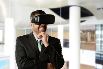 Mature Businessman wearing Virtual Reality Goggles