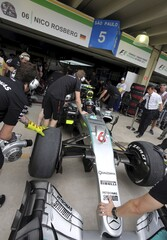Mechanics of Mercedes Formula One team push the car of driver Rosberg of Germany to the garage during the first free practice of the Brazilian F1 Grand Prix in Sao Paulo