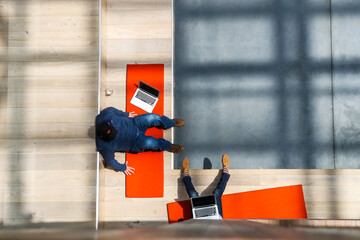 People are seen from above as they work together in the lobby of the Airbnb office headquarters in the SOMA district of San Francisco
