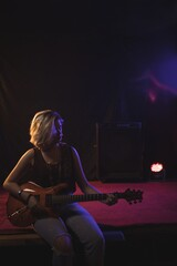 Female guitarist playing guitar while sitting on stage