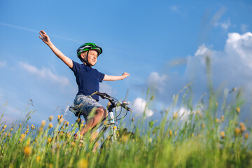 Happy boy ride a bicycle without hands and enjoy with sunlight