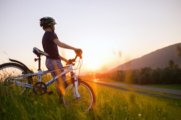 Boy with bicycle looks on sunset