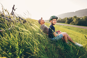 Father and son rest in high green grass after bicycle walk