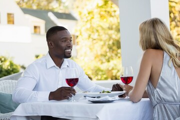 Young couple holding red wineglasses at restaurant