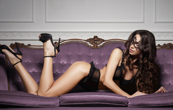 Beautiful and young woman posing in sexy lingerie and Venetian mask on violet sofa. Vintage interior and retro background.