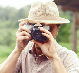 Young, handsome hippy taking pictures outdoors. Holiday, journey, trip, vacation concept.