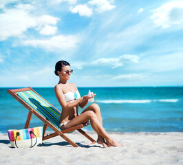Attractive young girl in bikini sunbathing on beach. Traveling, holiday, vacation concept.