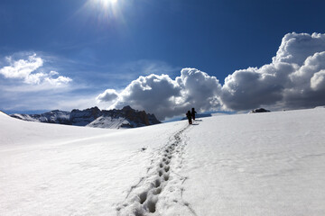 Footpath in snow and two hikers on snowy plateau at sun spring day