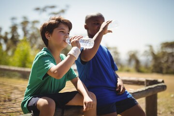 Boys drinking water after workout during obstacle course