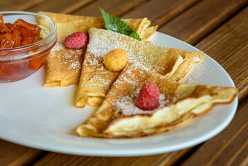 Crepes with jam, berries and sugar powder. Homemade pancakes, delicious breakfast