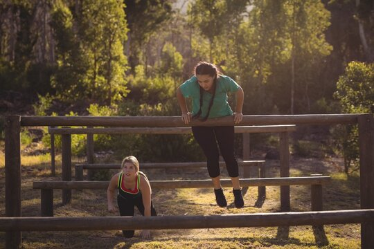 Women exercising on outdoor equipment during obstacle course