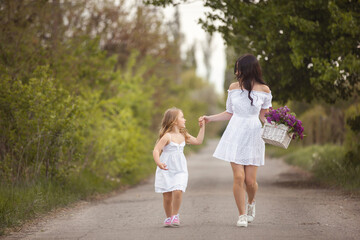 Young beautiful mother and little daughter having fun together. Pretty mom and cute girl outdoors. Cheerful family together rinning taking by the hand
