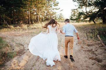 Just married couple walking in pine forest