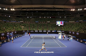 Spain's Feleciano Lopez hits a shot to Serbia's Novak Djokovic during a practice session with the roof closed due to hot temperatures, in Rod Laver Arena at Melbourne Park