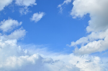 Blue sky and white fluffy clouds with a space for text - suitable for a background