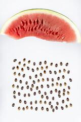 Raining seeds. Beautifully cut watermelon slice. Watermelon on white background. Beautiful ripe watermelon close-up.