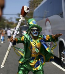 A man wearing the Brazilian colours and carrying a mock torch dances during the 2016 Rio Olympics torch relay in Rio de Janeiro