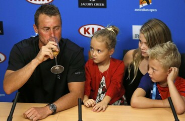 Australia's Hewitt drinks champagne during a news conference while his children watch after playing his last Australian Open singles match before his retirement, at the Australian Open tennis tournament at Melbourne Park