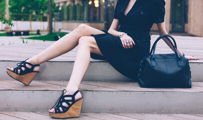 Girl sitting on the stairs with a big black super fashionable handbags in a dress and High Wedge Sandals on a warm summer evening