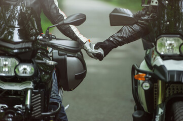 Two motorcyclists are holding hands while sitting on motorcycles, a man and woman in love, a common hobby
