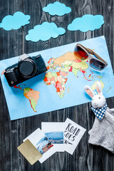 tourist outfit and camera with map for trip with kids dark wooden background top view mockup