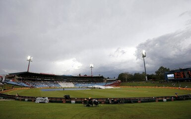 Workers cover the crease as clouds gather around the stadium during the fourth cricket test match between South Africa and England in Centurion