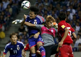 Japan's Kohrogi fights for the ball with Cambodia's Sou during their 2018 World Cup qualifying soccer match at Saitama Stadium in Saitama
