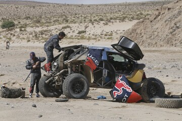 Loeb of France and co-pilot Elena work on their car after an accident which turned the car over during the eighth stage in the Dakar Rally 2016 near Belen