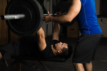 Man lifting weights with a trainer
