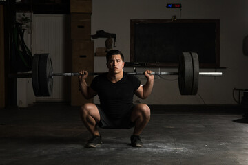 Athletic man donig barbell squats