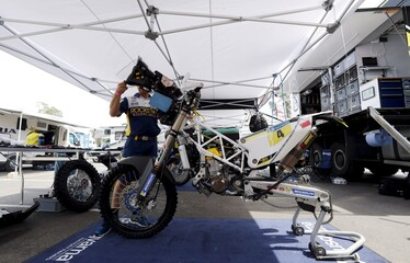 A mechanic works on the Husqvarna motorcycle of Quintanilla of Chile outside the technical verification area ahead of the Dakar Rally 2016 in Buenos Aires