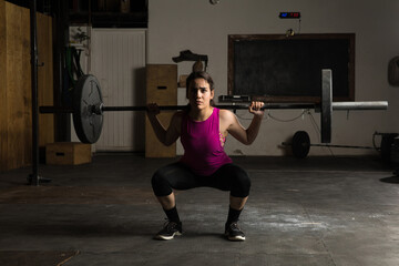 Woman doing barbell squats in a gym